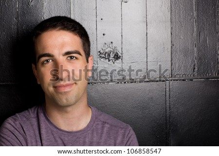 A cute young Caucasian adult leaning on black wall standing. Eyes are sharp and includes area for copy space. - stock photo