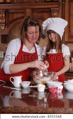 A cute young girl and her mother baking cupcakes together - stock photo