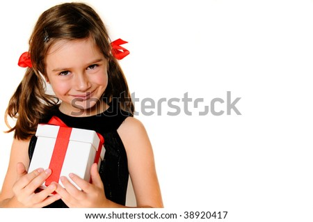 A cute young girl holding a christmas gift, copy space - stock photo