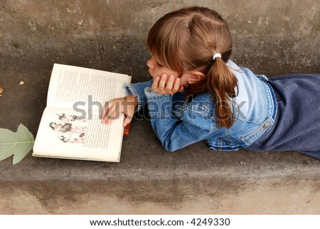 A cute young girl lying on a bench reading a book - stock photo