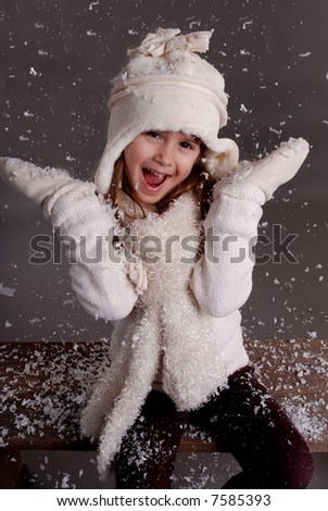 A cute young girl playing in the snow - stock photo