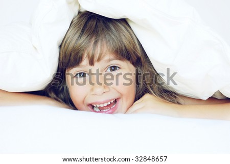 A cute young girl playing under the covers - stock photo
