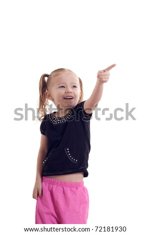 A cute young girl pointing to something, or touching something.  The image is isolated. - stock photo