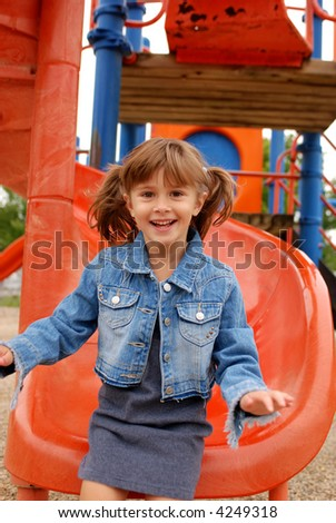 A cute young girl sliding down the slide - stock photo