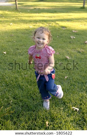 A cute young girl smiles as she runs in the grass at a park. - stock photo