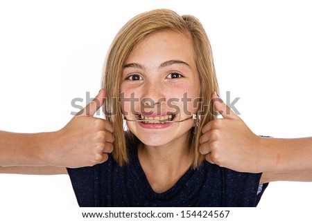 A cute young girl wearing orthodontic headgear - stock photo