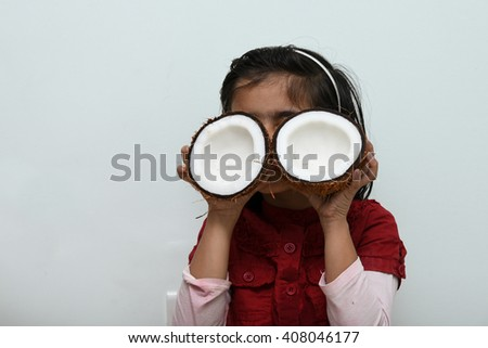 A cute young / small / little Indian girl/ kid/ child holding coconut cut open, Kerala, India. farm fresh organic tropical fruit, smiling daughter, goggles, coco, cream, milk, coconut oil healthy skin - stock photo