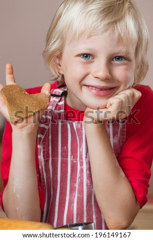 A cute young very proud boy is holding up a gingerbread love heart cookie he just baked - stock photo