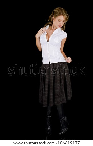A cute young woman posing seductively in her white shirt and plaid skirt. - stock photo