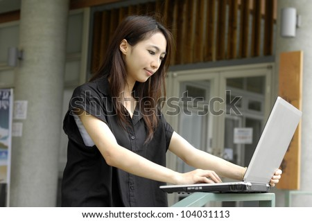 A cute young woman working on her laptop computer at college - stock photo