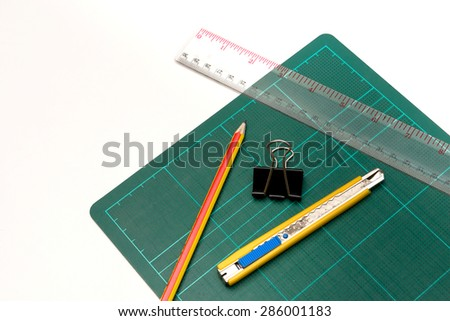 A cutter, clip, ruler, pencil over a white background - stock photo