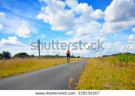 A cyclist on an empty rural road on a sunny day - stock photo