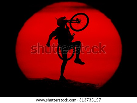 A cyclist travels through alpine hills and stands against a background of sunset with a mountain bike  - stock photo
