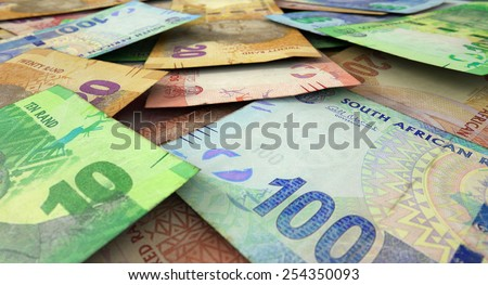A 3D rendering of a macro close-up view of a messy scattered pile of south african rand banknotes - stock photo