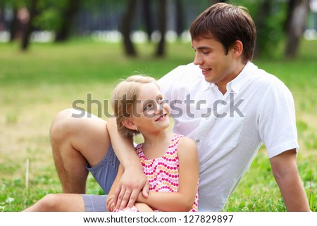 A dad and his daughter are together in the park - stock photo
