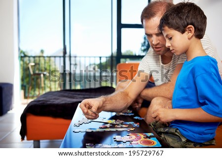 A dad and his son bonding over piecing a puzzle together - stock photo