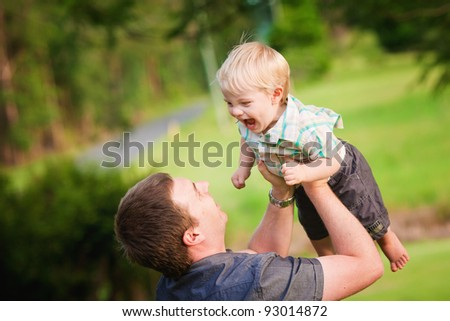 A Dad plays with his little boy in the outdoors in summer. - stock photo