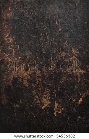 A dark brown background texture created from an old book with a hard leather cover with a worn out looking pattern. - stock photo