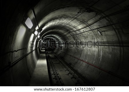 A dark grungy subway tunnel with tracks. - stock photo