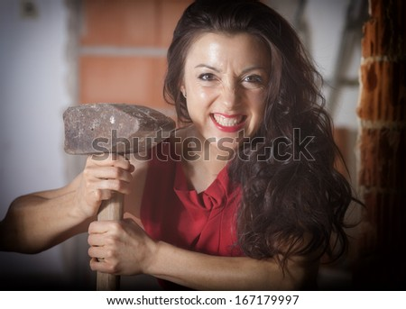 A darkhaired girl in a red dress hold a big sledgehammer in her hand. Snarling teeth. - stock photo