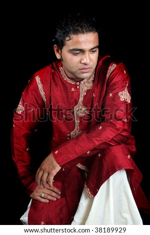 A daydreaming Indian man in a traditional attire, on black studio background. - stock photo