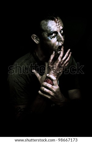 A decaying zombie feeds on a severed bloody human hand in the darkness of midnight in a deadly midnight snack conceptual - stock photo