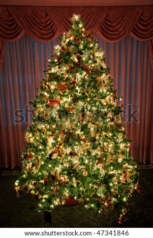 A decorated and lighted indoor Christmas tree - stock photo