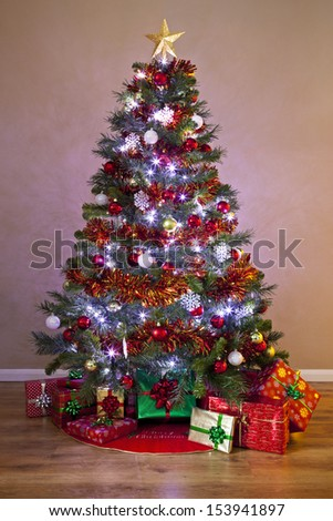 A decorated Christmas tree in a home, lit up with fairy lights and surrounded by gift wrapped presents. - stock photo