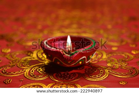 A decorative Diwali lamp against glittering background - stock photo