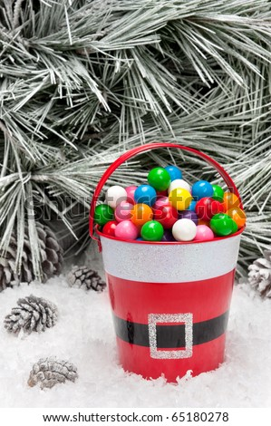 A decorative pail of Christmas candy in a snowy wilderness.  Open space for copy intentionally left in the upper image tree area. - stock photo