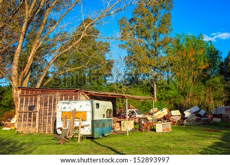 A decrepit barn with a lot of junk outside in Uribelarrea, Argentina - stock photo