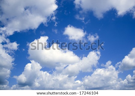 A deep blue sky and perfect cottony clouds - stock photo