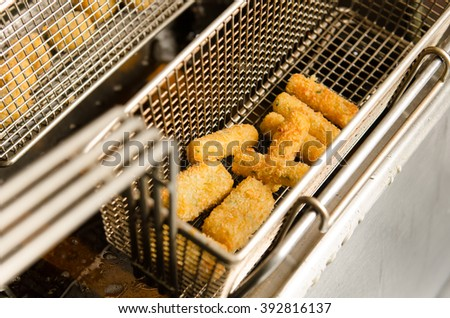 A deep pan industrial kitchen oil fryer, with golden oil, bubbling and frying potatoes - stock photo