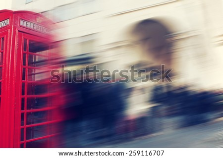 a defocused blur background of people walking in a street in London, United Kingdom, with a typical red telephone booth in the foreground - stock photo