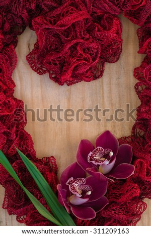 A delicate, red, heart shape on a wooden background with a couple red orchids and glasses. Great photo for valentines day, wedding invitations, or other creative ideas and concepts. Vertical format. - stock photo
