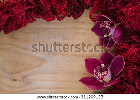 A delicate, red, scarf on a wooden background with a couple red orchids. This would be a great photo for valentines day, wedding invitations, wallpapers, cards, or other creative ideas and concepts. - stock photo