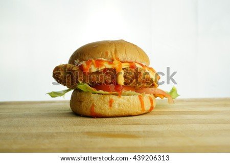 A delicious crispy chicken burger combined with cheese, lettuce and tomato on white background - stock photo