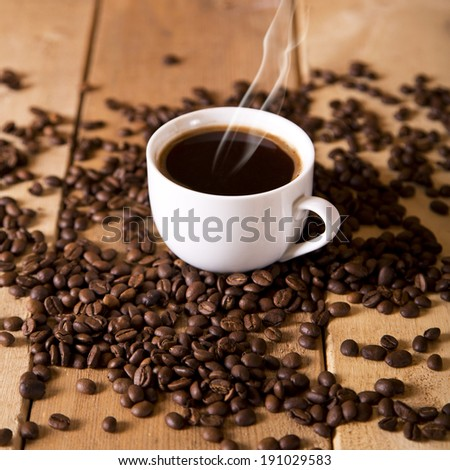 A delicious cup of coffee on a table with roasted coffee beans - stock photo