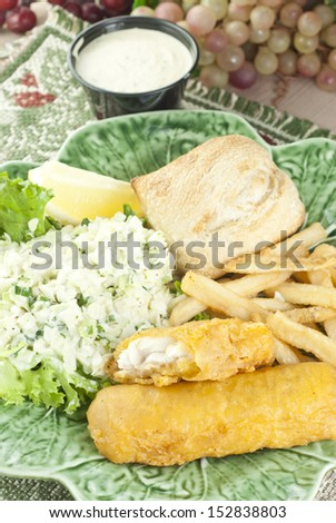 A delicious fish and chips dinner, served with fresh coleslaw, vertical full frame image - stock photo
