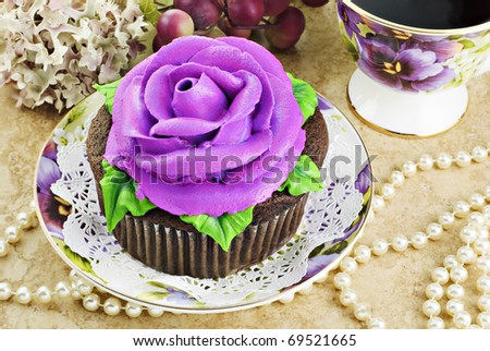 A delicious fresh baked cupcake decorated with a purple frosting rose - stock photo