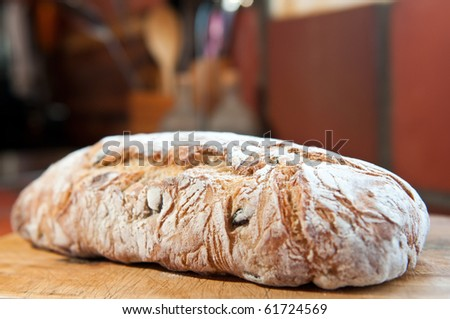 A delicious freshly baked olive bread on a wooden slicing board. - stock photo