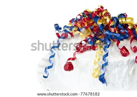 A delicious homemade party cake with colorful ribbons on a cake stand with white background, selective focus - stock photo
