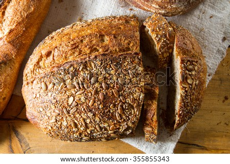 A delicious loaf of brown multigrain bread and baguettes, fresh out of the oven. - stock photo