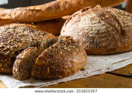 A delicious loaf of brown multigrain bread, with sourdough bread and baguettes in the background, fresh out of the oven. - stock photo