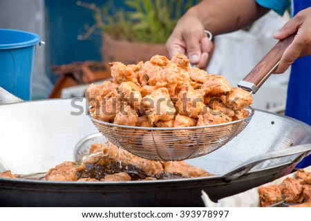 A delicious-looking spicy fried food or fried fish patty freshly fished from a boiling pan from a roadside food stall in Thailand - stock photo