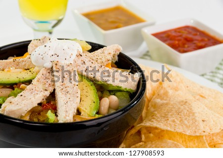 A Delicious Mexican Taco Salad Bowl with Rice, Lettuce, Pinto Beans, Avocado, Cheese, Red and Green Salsa, Sour Cream, and Strips of White Chechen - stock photo