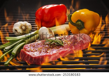 A Delicious New York Stake on a Flaming Hot Grill with Red and Yellow Peppers, garlic and onions - stock photo