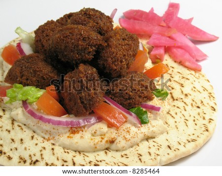 A delicious portion of falafels served on top of a pita bread with hummus, lettuce, tomato, red onions, and a side of turnips pickled in beet roots. - stock photo