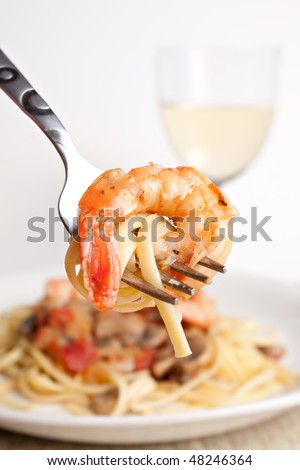 A delicious shrimp scampi pasta dish along with a glass of pinot grigio white wine.  Shallow depth of field with focus on the fork and shrimp. - stock photo