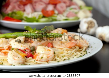 A delicious shrimp scampi pasta dish with antipasto salad in the background - stock photo